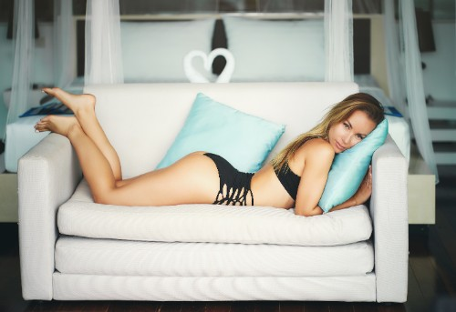 ソファの上で寝そべる下着姿の女性